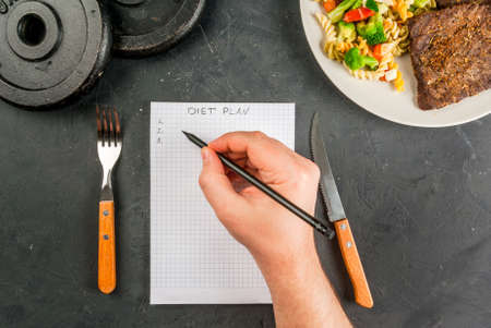 supervise: Concept of dieting, counting calories: a plate of healthy food (whole grain pasta with vegetables); man fills out a food diary. Hands in picture, top view, copy space