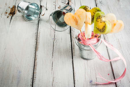 Idea for the congratulations Valentine: a bouquet of fruit (kiwi, apple, pear), carved in the form of hearts, with gift ribbon in a decorative bucket, on a wooden table, copy space top view Stock Photo