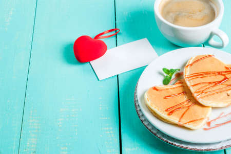 Breakfast on Valentines Day: Pancake in the form of hearts with red sauce, a cup of coffee, a note or love confession and a red plush heart toy. On a light blue wooden table, copy space