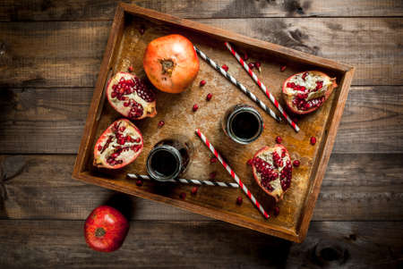 Homemade pomegranate juice in bottles in a wooden tray, with straws and fresh whole and sliced pomegranates. top view, copy space