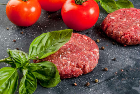 Fresh raw home-made minced beef steak burger with spices, tomatoes and basil, on a stone table, copy space, top view Reklamní fotografie - 70852445