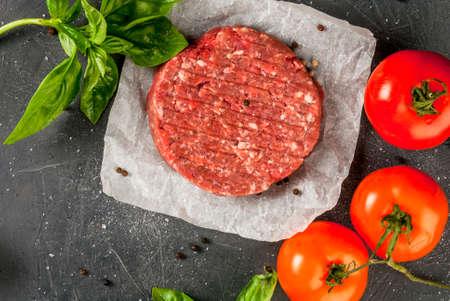 Hamburger casalingo crudo crudo della bistecca di manzo tritato con le spezie, i pomodori e basilico, su una tavola di pietra, spazio della copia, vista superiore