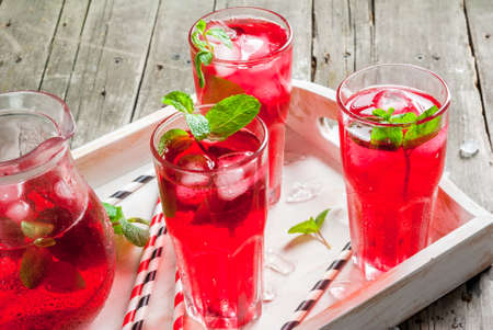Summer iced drink - tea or juice with ice and mint. On rustic wooden table, with white tray, copy space, close view