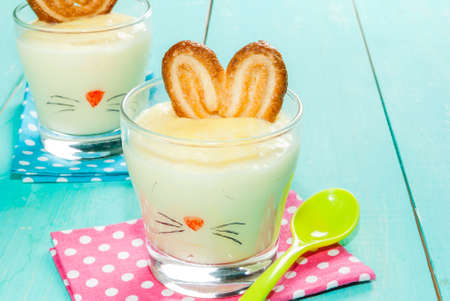 aliments droles: Funny food for children at Easter: dessert panna cotta (pudding) in the glass, decorated with a bunny, with ears of cookies, copy space Banque d'images