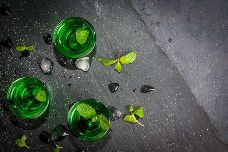 liquor: Sweet refreshing mint liqueur, with ice and mint leaves on the slate tray to feed on gray concrete stone table, top view, copy space