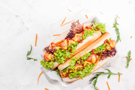 Homemade hot dogs with sausages, fresh lettuce, cucumbers, herbs, mustard and ketchup. On the white stone concrete table top view, copy space