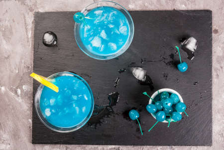 Party, cocktails blue lagoon or blue curacao on a slate tray on concrete stone table top view