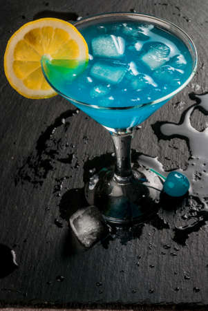 Party, cocktails blue lagoon or blue curacao on a slate tray on concrete stone table copy space Stock Photo