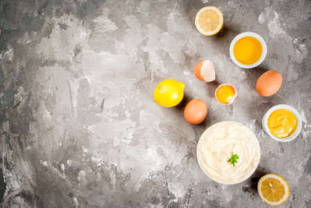 Mayonnaise with ingredients for cooking - eggs, vegetable oil, mustard, lemon, parsley. On the grey stone concrete table top view copy space Banco de Imagens