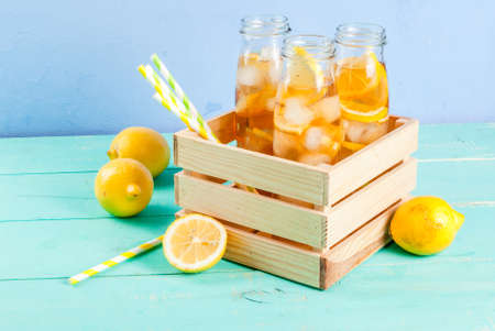 Iced summer drink - tea with lemon on a blue wooden table, in bottles with striped straws copy space Stock Photo