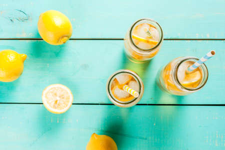 Iced summer drink - tea with lemon on a blue wooden table, in bottles with striped straws copy space top view Stock Photo