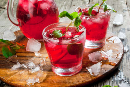 rooibos: Summer iced drink - tea or juice with ice and mint. On rustic wooden table, copy space