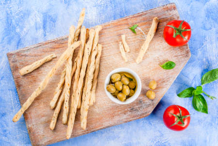 gressins: Lunch or snack in the Italian style: grissini breadsticks, oil with olives, tomatoes and basil. On a light blue stone table, top view copy space Banque d'images