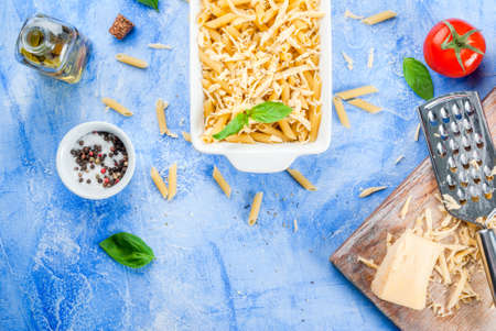 Macaroni with grated cheese in a pot ready to bake; grater and grated cheese on a cutting board, spices and tomatoes. On a light blue stone concrete table top view copy space Reklamní fotografie