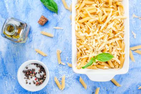 Macaroni with grated cheese in a pot ready to bake; spices and tomatoes. On a light blue stone concrete table top view copy space