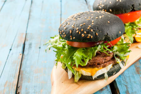 Freshly homemade black burgers with cheese, beef minced steak, tomato and lettuce. Summer sunny, old light blue rustic table, copy space Stock Photo