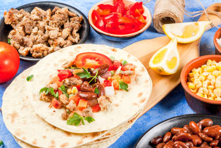 Cooking street fast Mexican food, freshly prepared, homemade sandwiches burrito with beans, beef, corn, peppers, tomatoes and herbs. On the blue background of concrete stone, close view copy space