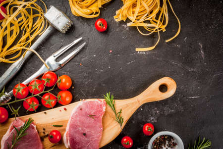 Preparations for cooking dinner. Fresh raw pork, steaks, on cutting shale board on a black table. With hammer to beat meat and fork, with spices, fresh raw pasta and tomatoes, top view copy space Stock Photo