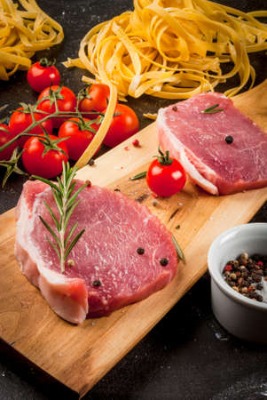 Products for cooking dinner. Fresh raw pork, steaks, on cutting shale board on a black table. With hammer to beat meat and fork, with spices, fresh raw pasta and tomatoes, close view vertical