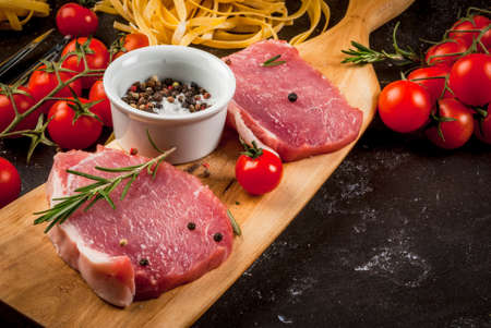Products for cooking dinner. Fresh raw pork, steaks, on cutting shale board on a black table. With hammer to beat meat and fork, with spices, fresh raw pasta and tomatoes, close view copy space