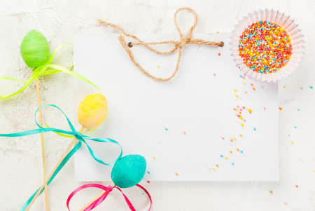 Funny childrens food for Easter, decoration. Sweets pop cake on a stick, with colorful ribbons, sugar sprinkles for biscuits and a notebook for congratulations. On a white table, top view, holiday background,, copy space