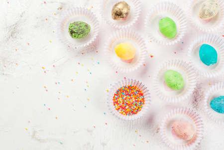 부활절, 장식 재미있는 어린이 음식. 흰색 부엌 테이블에 컵 케이크에 대한 종이 형태로 설탕 뿌리와 계란의 형태로 초콜릿 과자를 장식하는 것에 대한 스톡 콘텐츠