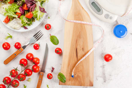Concept of weight loss and healthy eating: a light salad of green leaves and tomatoes, centimeter tape and scales. On a white concrete table, copy space top view