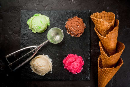 sorts: Selection of colorful home made ice cream: lemon (pistachio) green, berry pink, chocolate, white vanilla. With a spoon for balls, waffle cones, on a slate board, on a black table. Top view, copy space