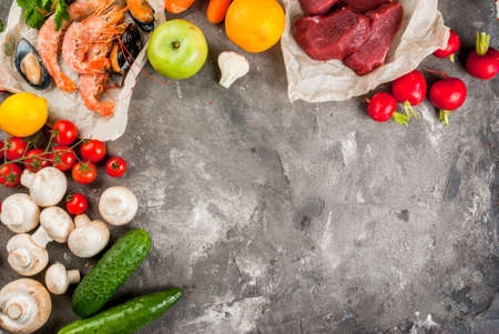 Selection of healthy dietary food products - raw beef, seafood, vegetables, fruits and greens. On a concrete gray table, top view copy space
