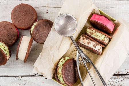 Selbstgemachtes Eis-Sandwich mit Schokoladen-Cookies Whoopie-Torte. Mit Beeren, Vanille und Minze-Eis, ergänzt mit Schokoladen-Chips. Auf einem weißen Holztisch. Draufsicht Standard-Bild