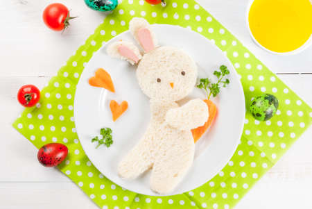 Funny food for children for Easter: breakfast, a sandwich in the form of a bunny with carrots, with juice, bright multi-colored quail eggs, tomatoes. top view