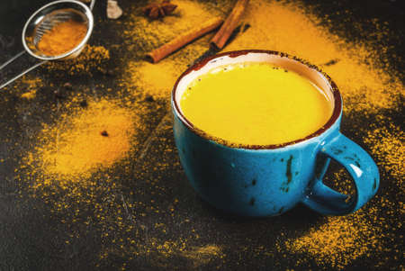 Traditional Indian drink turmeric milk is golden milk with cinnamon, cloves, pepper and turmeric. On a concrete table, with spices on the background. In a large cup, Copy space, toned