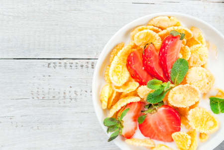 Summer light breakfast: homemade organic yogurt with cornflakes and fresh strawberries. On a white rustic wooden table copy space top view Stock Photo