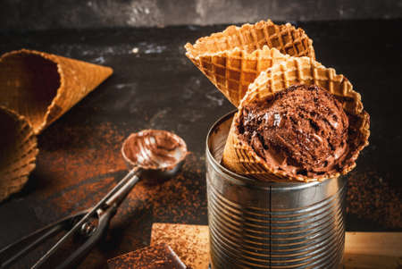 Homemade chocolate ice cream in waffle cones, with a spoon for ice cream, cocoa and pieces of dark chocolate. In an aluminum can as a stand. On a dark gray table, rustic. Copy space close view Stock Photo