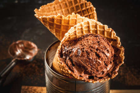 Homemade chocolate ice cream in waffle cones, with a spoon for ice cream, cocoa and pieces of dark chocolate. In an aluminum cancan as a stand. On a dark gray table, rustic. Copy space close view Stock Photo