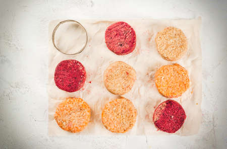 Dietary organic homemade raw vegan cutlets for burgers - with beets, with carrots and chickpeas. Top view, on a white concrete table, with a form for cooking cutlets.