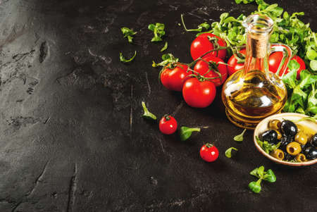 Ingredients of Italian cuisine. Selection of products for salad. Olive oil, lettuce leaves, tomatoes. On a black dark shale concrete stone kitchen table. Horizontal copy space