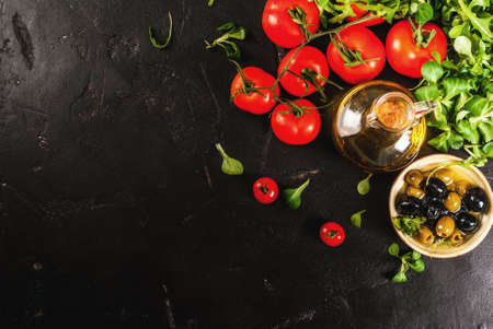 Ingredients of Italian cuisine. Selection of products for salad. Olive oil, lettuce leaves, tomatoes. On a black dark shale concrete stone kitchen table. Horizontal copy space top view Stock Photo