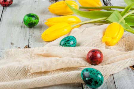 Spring Holiday Easter: colored eggs and flowers tulips on the wooden table, copy space Stock Photo
