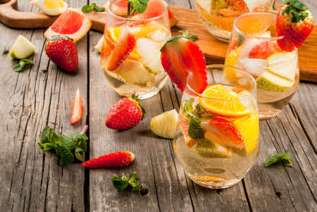 Traditional summer drink white sparkling sangria. With champagne, strawberries, oranges, lemon, green apple and grapefruit. On a wooden rustic table, with a jug and ingredients. Copy space
