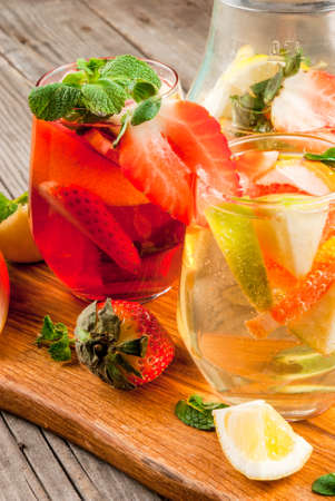 Traditional summer drink sangria - red, pink and white. With champagne, pink and red wine, strawberries, oranges, lemon, green apple and grapefruit. On a wooden rustic table, close