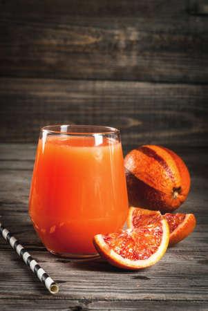 Verfrissend zomerdrankje. Sap van rode Siciliaanse sinaasappelen. Op een rustieke houten tafel, met hele en gesneden sinaasappels. Ruimte kopiëren