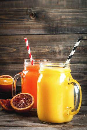 Verfrissend zomerdrankje. Sap van klassieke sinaasappelen en rode Siciliaanse sinaasappelen. Op een rustieke houten tafel, met hele en gesneden sinaasappels. Ruimte kopiëren Stockfoto