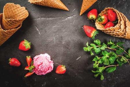 Roze aardbeien-ijs. In een kleine kom, op de zwarte betonnen tafel met ijshoorntjes, een bosje munt en aardbeien, bovenaanzicht, kopie ruimte, frame