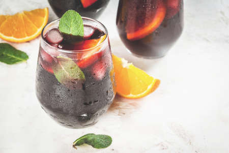 Traditional Spanish summer refreshing drink, cocktail, Tinto de verano. With wine, ice and pieces of fresh orange. On white stone  table, copy space