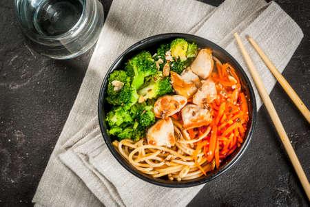 Gezond eten, dieet. Boeddha schaal hete salade in Aziatische stijl: noedels met sojasaus, pittige worteltjes, kip, broccoli. Op zwarte betonnen stenen tafel, met eetstokjes en water. Bovenaanzicht kopie ruimte