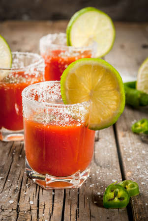Mexican traditional alcohol drink. Sangrita, with tequila, tomato juice, hot spices, chili and lime.Analogous bloody mary. On rustic wooden table, copy space