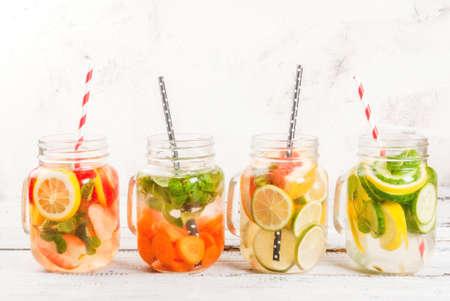 Selección de aguas refrescantes de dieta de desintoxicación infundida: con pepino y limón, con zanahorias y menta, con lima y pomelo, con fresas y limón. En la mesa de madera blanca, en el espacio de copia Mason Jar