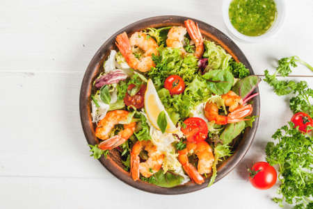 Seafood. Shellfish. Fresh lettuce salad with tomatoes, herbs and grilled fried shrimps prawns, on white table, top view, copy space Stock Photo