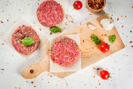 Fresh raw home-made minced beef steak burger with spices, tomatoes and basil, on a white stone concrete table, Stock Photo